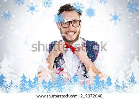 Geeky hipster wearing christmas vest against snowflakes and fir trees - stock photo