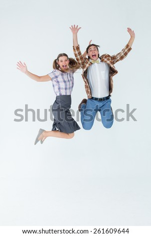 Geeky hipsters jumping and smiling on white background