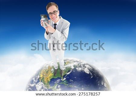 Geeky smiling businessman showing calculator against blue sky over clouds