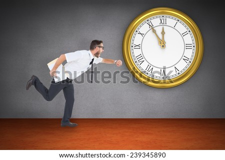 Geeky young businessman running late against room with wooden floor - stock photo