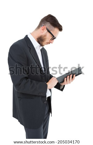 Geeky young man reading from black book on white background