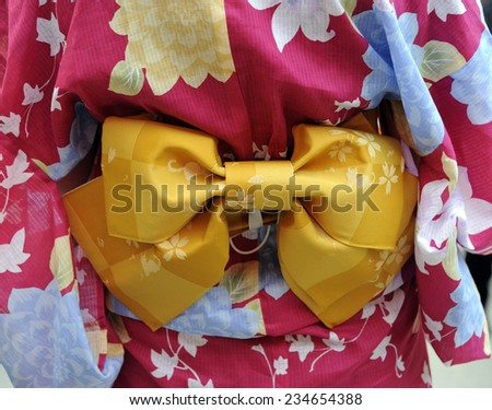Geisha in pink kimono with yellow munsuko. This is a traditional Japanese dress
