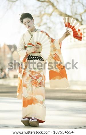 geisha with orange fans dancing outdoors - stock photo