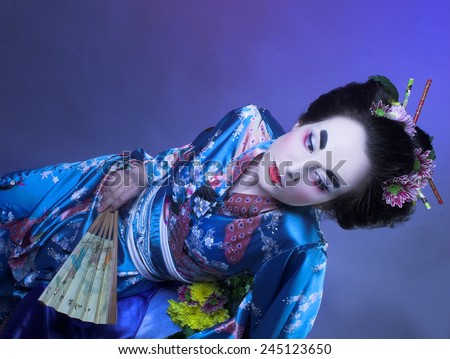 Geisha. Young woman in blue kimono with fan and with flowers in her hair. - stock photo
