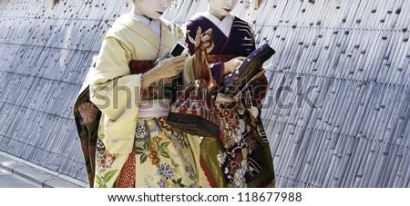 Geishas walking by an old street, osaka, japan - stock photo