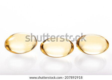 Gelatin capsules with fish oil on white background - stock photo