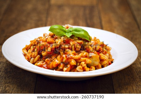 Gemelli pasta with homemade tomato and zucchini sauce garnished with fresh basil leaves. Sprinkle with parmesan cheese.  - stock photo