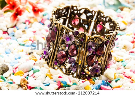 Gems bracelets on stone background. - stock photo