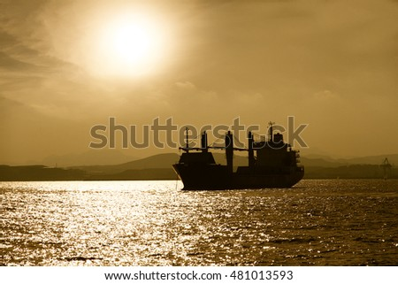 General cargo vessel anchored in Alicante bay during the sunset