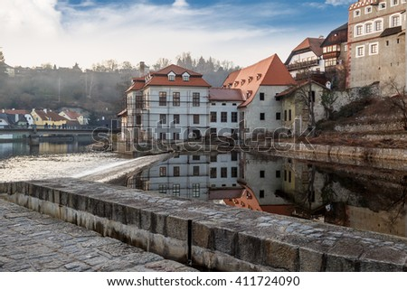 General Cesky Krumlov view with historical small houses along the river, on cloudy blue sky background.