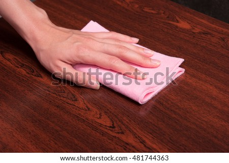 General cleaning of the house. Wiping wooden shelf from dust. Housewife wipes surface with pink cloth.