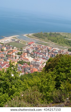 General top view of Ayancik town in Sinop in Black Sea region inside green trees with blue sea, on bright sky background. - stock photo