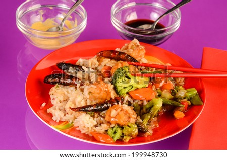 General Tso's Chicken Dinner on red plate with chopsticks against purple reflective background with horseradish mustard and soy sauce. - stock photo