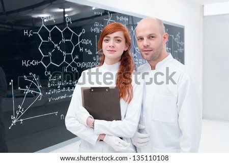 general-view of a teacher and a student in a chemistry lab smiling in the camera and a blackboard on the background