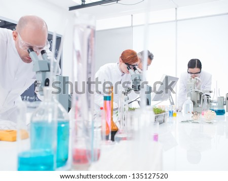 general-view of people  in chemistry lab analyzing under microscope on a lab table with colorful liquids and lab tools - stock photo