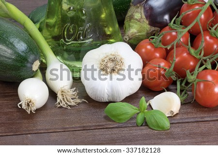 General view of the zucchini; eggplant, garlic, onion, basil leaves  and cherry tomatoes lying on a wooden table. Bottle with inscription Oil is in the background. - stock photo