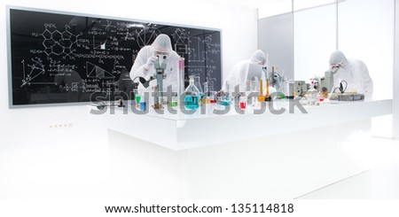 general-view of three people analysing  substances in a chemistry lab using colorful liquids and lab tools with a blackboard with chemical formulas on the background - stock photo