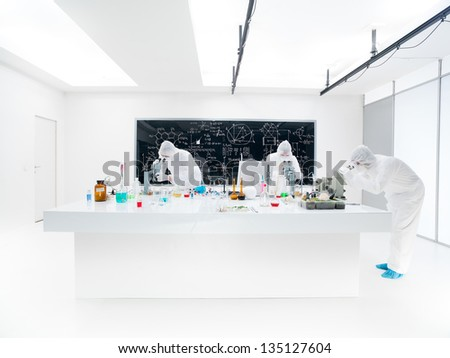 general-view of three scientists in a chemistry lab analyzing under microscope on a lab table with colorful liquids and lab tools with a blackboard on the background - stock photo
