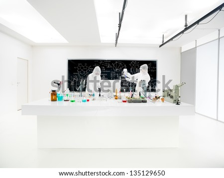general view of two scientists in a chemistry lab conducting an experiment around a lab table with colorful liquids, lab tools and magic gas with a blackboard on the background - stock photo