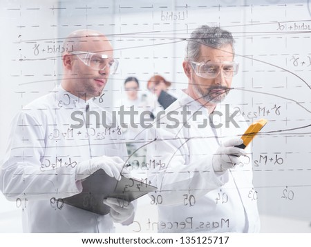 general-view of two scientists scaning and analyzig formulas on a transparent board with two students on the background