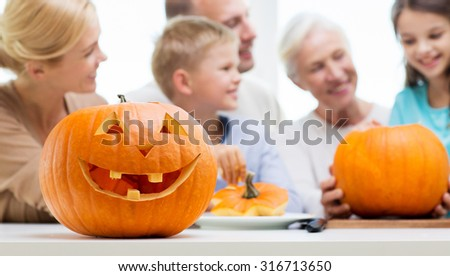 generation, holidays and people concept - helloween pumpkin lantern over happy family at home - stock photo