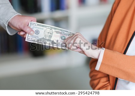 Generational conflict, old woman and young woman pulling on a dollar money bill. - stock photo