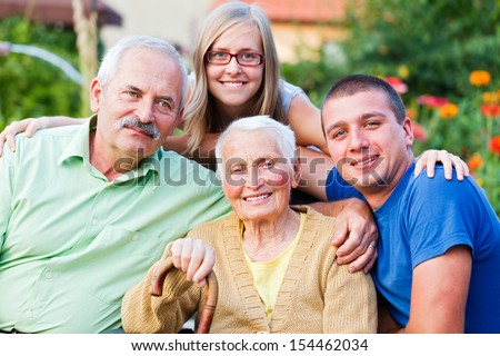Generations in one image: grandmother, son and young grandchildren in the garden of the nursing home. - stock photo