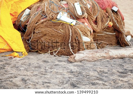 Generic horizontal color capture of a fish farming nets wrapped and stored overnight under a yellow tarpaulin on the sands at  Manaputta Beach, Pondicherry, Tamil Nadu, India - stock photo