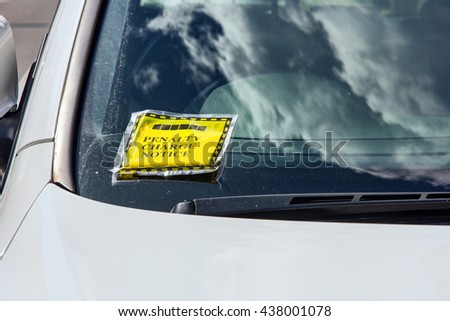 Generic penalty charge notice (parking fine) attached to windscreen of white car parked on street in London England - stock photo