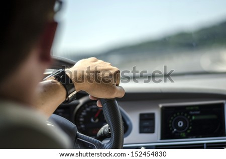 Generic photo of man driving a car through slight turn. - stock photo
