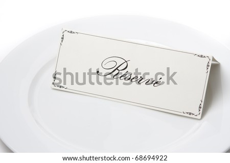 Generic reserved sign card on a white plate - stock photo