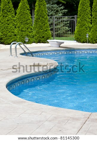Generic small fenced swimming pool with diving board - stock photo