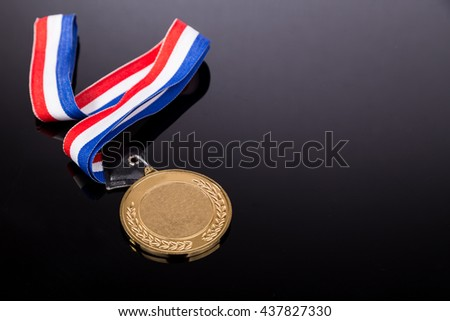 Generic sporting event gold medal with red and blue ribbon on dark background - stock photo