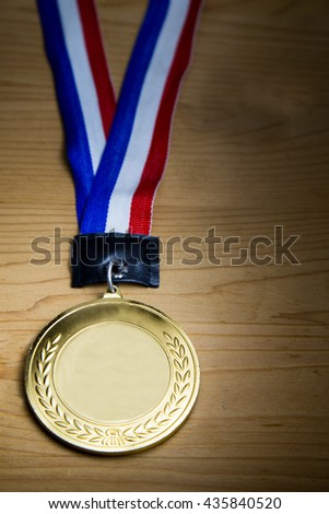 Generic sporting event gold medal with red and blue ribbon on wooden surface, again ray of lights. Fine art rendition. - stock photo