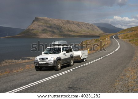 Generic SUV with a trailer in motion next to Hvalfjordur fiord in Iceland - stock photo