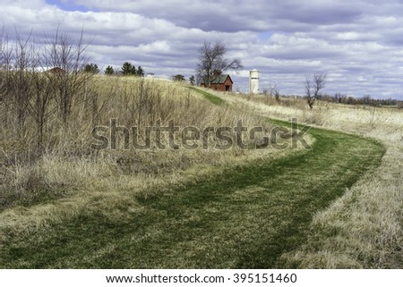 GENEVA, ILLINOIS/USA - MARCH 20, 2016: Part of an historic farmstead is seen beyond a grassy bend in Lake View Trail at Peck Farm Park, a 385-acre nature retreat in this far western suburb of Chicago. - stock photo