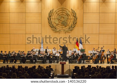 GENEVA - JANUARY 22: Antoine Marguier conducts the United Nations Orchestra at the UN Palais January 22, 2013 in Geneva, Switzerland celebrating the 50th anniversary of the Elysee Treaty. - stock photo