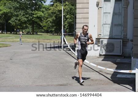 GENEVA - JULY 21: Aurelien Labrun, the winner of the mens 2013 Geneva ITU Triathlon European Cup competes in the running section July 21, 2013 in Geneva, Switzerland - stock photo