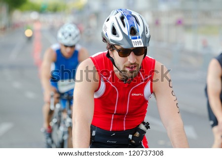 GENEVA - JULY 22: Unidentified athletes competing in the cycling section of the 2012 ITU Triathlon European Cup, July 22, 2012 in Geneva, Switzerland - stock photo
