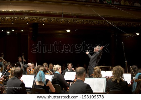 GENEVA - JUNE 23:   Antoine Marguier conducts the United Nations Orchestra at the Victoria Hall June 23, 2013 in Geneva, Switzerland. - stock photo