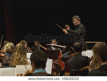 GENEVA - JUNE 24: Conductor Antoine Marguier conducts the United Nations Orchestra at the Victoria Hall June 24, 2012 in Geneva, Switzerland. - stock photo