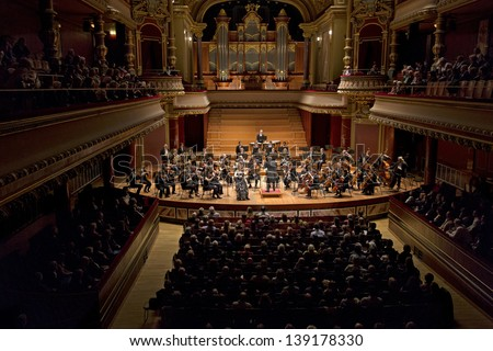 GENEVA � MARCH 20: Soloist violinist Solenne Paidassi playing with the United Nations Orchestra conducted by Antoine Marguier at the Victoria Hall March 20, 2013 in Geneva, Switzerland. - stock photo