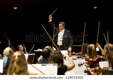GENEVA - NOVEMBER 17: Conductor Antoine Marguier conducts the United Nations Orchestra at the Victoria Hall, November 17, 2012 in Geneva, Switzerland. - stock photo