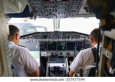 GENEVA - SEPTEMBER 11: Etihad Regional pilots in aircraft cockpit on September 11, 2014 in Geneva, Switzerland. Darwin Airline, operating under the brand name Etihad Regional since January 2014 - stock photo