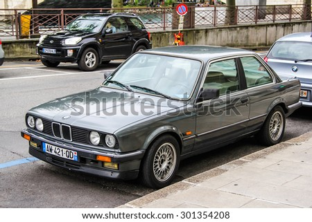 GENEVA, SWITZERLAND - AUGUST 4, 2014: Grey classical car BMW E30 3-series at the city street. - stock photo
