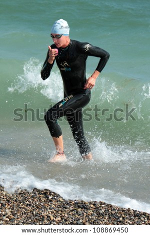 GENEVA, SWITZERLAND - JULY 22 : unidentified female athlete going out of water at the International Geneva Triathlon, on July 22, 2012 in Geneva, Switzerland. - stock photo
