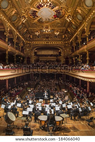 GENEVA, SWITZERLAND � MARCH 21, 2014: Antoine Marguier conducts the UN Orchestra accompanied by pianist Elisso Bolkvadze at the Spring Concert 2014 in the  Victoria Hall. - stock photo