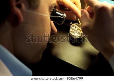 GENEVA, SWITZERLAND - NOV.13:  A Swiss watchmaker concentrates on assembling fine parts of a watch at The Watches Day, an exhibition of Swiss watchmakers November 13, 2011 in Geneva, Switzerland - stock photo