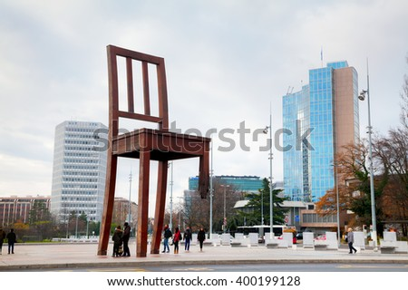 GENEVA, SWITZERLAND - NOVEMBER 28: Broken Chair monument near United Nations palace with tourists on November 28, 2015 in Geneva, Switzerland. - stock photo