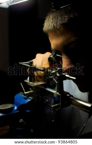 Geneva, Switzerland - November 13, 2011: Swiss watchmaker using lathe to grind, shape a tiny hand-made watch part during The Watches Day, an annual exhibition of watchmakers